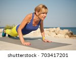 young athletic woman exercising ... | Shutterstock . vector #703417201