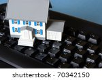 A miniature house with the word home spelt on the keyboard for many conceptual meanings. - stock photo