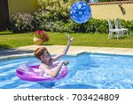 A teenage boy in a pink, inflatable ring, catching a ball in a swimming pool - stock photo
