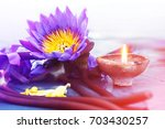 a lotus flower and a candle in... | Shutterstock . vector #703430257