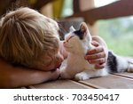 Stock photo little cute boy with blonde hair lying on a wooden floor on a balcony embracing a small cat 703450417