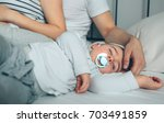 Small photo of Baby asleep while his parents caress him