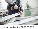 manual worker assembling pvc... | Shutterstock . vector #703569295