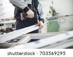 manual worker assembling pvc... | Shutterstock . vector #703569295