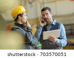 male manager in hard hat making ... | Shutterstock . vector #703570051