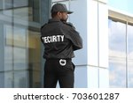 male security guard standing... | Shutterstock . vector #703601287