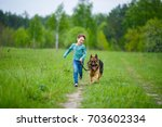 Stock photo a little boy runs through the green meadow with his big german shepherd dog the wind blows his hair 703602334