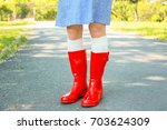 young woman in red wellington... | Shutterstock . vector #703624309
