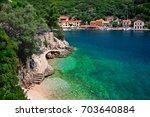 tiny little beach next to kioni ... | Shutterstock . vector #703640884