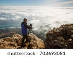 man standing with a tripod and... | Shutterstock . vector #703693081