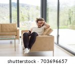 handsome casual young man using ... | Shutterstock . vector #703696657