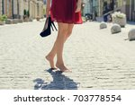 Woman in red elegant dress, holding high heel shoes in hand and walking in the city barefoot; close up photo of woman