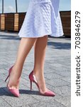 Small photo of Beautiful slender legs tanned skin is shod in high-heeled shoes depilation body care catologue stylish fashion collection walks on the street health body care cream white dress denim jacket.