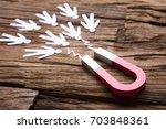 closeup of magnet attracting... | Shutterstock . vector #703848361