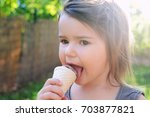 little girl eating ice cream... | Shutterstock . vector #703877821