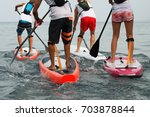 stand up paddle group on the sea | Shutterstock . vector #703878844