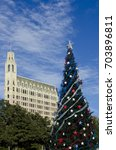 Small photo of A Christmas tree decked out in red, white and blue stars of Texas stands in Alamo Plaza, with the Gothic architecture of the Emily Morgan Hotel building dominating the San Antonio skyline.