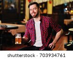 cute young man in a plaid shirt ... | Shutterstock . vector #703934761