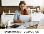 Small photo of Candid shot of worried young European female dressed casually sitting at kitchen table, holding paper sheet and talking to house and utilities service representative about miscalculation in bills