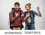 Small photo of Portrait of agitated young couple with rucksacks gesturing actively, trying to explain themselves while being late for plane, looking worried. Body language. Tourism, travel and adventure concept
