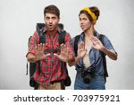 Small photo of Picture of stylish young European male and female tourists, travelers or adventures looking frustrated and worried, showing stop gesture with hands, trying to settle down conflict while traveling