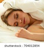 pretty woman lying down on her... | Shutterstock . vector #704012854