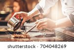 hand of man take cooking of... | Shutterstock . vector #704048269