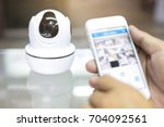 male hand press phone watch cctv | Shutterstock . vector #704092561