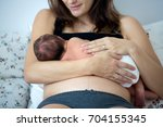 young mother breastfeeds her... | Shutterstock . vector #704155345