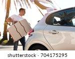man traveler putting suitcase... | Shutterstock . vector #704175295