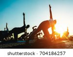 silhouette of people doing yoga ... | Shutterstock . vector #704186257