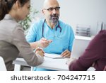male doctor talking to young... | Shutterstock . vector #704247715