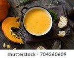 pumpkin cream soup in bowl on... | Shutterstock . vector #704260609