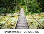old wooden plank bridge across... | Shutterstock . vector #704282407