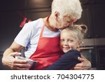 grandmother kissing and hugging ... | Shutterstock . vector #704304775