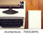old typewriter with notepad on... | Shutterstock . vector #704318491