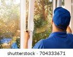 worker installing new plastic... | Shutterstock . vector #704333671