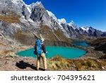 hiking scene in cordillera... | Shutterstock . vector #704395621