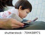 child girl playing smartphone | Shutterstock . vector #704438971