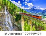 Zermatt, Switzerland. Gornergrat tourist train with waterfall, bridge and Matterhorn. Valais region.