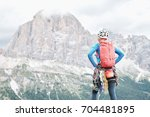 Small photo of Female mountaineer with backpack, helmet and harness with climbing gear enjoying stunning view to mount Tofana di Rozes before ascent during summer day in Dolomite Alps - adventure concept