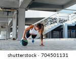 woman doing push ups with the... | Shutterstock . vector #704501131