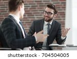 manager talking with a colleague | Shutterstock . vector #704504005