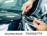 worker hands installs car paint ... | Shutterstock . vector #704504779
