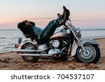 man sleeping on a motorcycle on ... | Shutterstock . vector #704537107