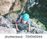 A Little Boy Climbs On Cliff....