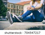 young woman sitting on city... | Shutterstock . vector #704547217
