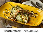 cheese stuffed roasted poblano... | Shutterstock . vector #704601361