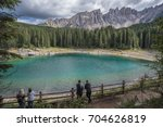 Small photo of Visitors marveling the small alpine Lake of Carezza, its marvelous colors and Latemar mountain massif peaks in the background, Dolomites, Nova Levante village, Trentino, Alto-Adige, South Tyrol, Italy