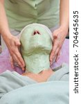 Small photo of Hands applying alginate face mask. Work of cosmetician, skin treatment.
